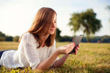 adult woman: Beautiful young woman with digital tablet in park
