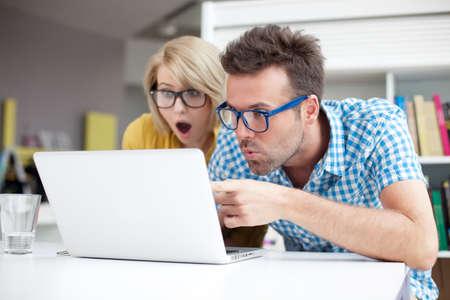 surprised: Dos estudiantes sorprendidos aprendizaje en la biblioteca en la computadora portátil