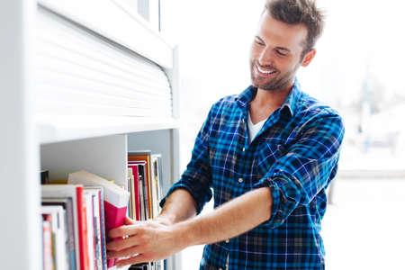 persona feliz: El estudiante que elige el libro en la biblioteca de atril Foto de archivo