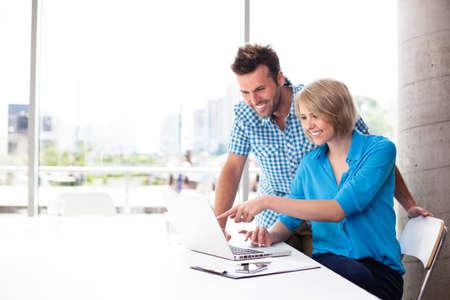 Couple de travail sur ordinateur portable dans le bureau