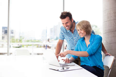 Couple working on laptop in office