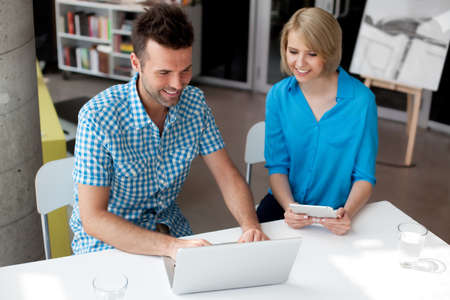two people meeting: Designers working on laptop and digital tablet in the coworking office Stock Photo