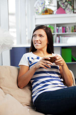 couch: Woman with coffee sitting on couch