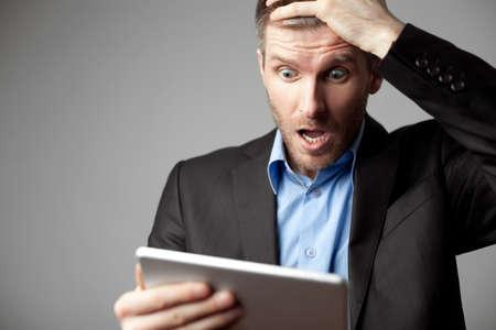 デジタル タブレットでショックを受けたビジネスマン 写真素材