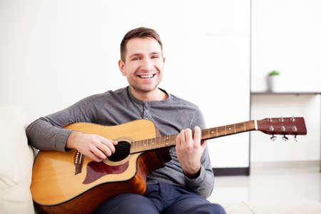 man playing guitar: Handsome young man playing guitar, sitting on sofa