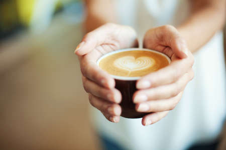 Closeup of Female holding coffee with heart symbol