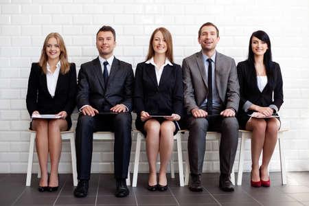 gente sentada: Grupo de hombres de negocios felices que se sientan en las sillas