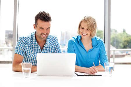 幸せなビジネス パートナーのラップトップに取り組んで。チームワーク、概念をコワーキングします。