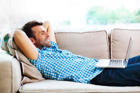 Man relaxing with laptop on couch Фото со стока