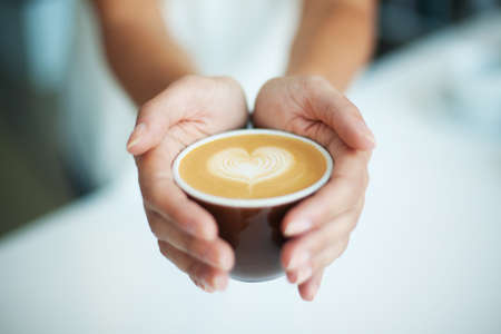Female giving coffee with heart symbol