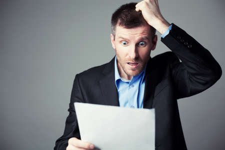 terrified businessman reads contract and pulls his hair from head Foto de archivo