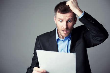 verängstigt Geschäftsmann liest Vertrag und zieht seine Haare vom Kopf