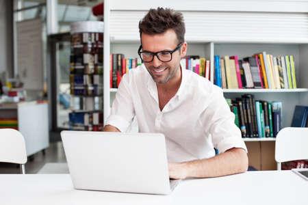 Hombre feliz que trabaja en la computadora portátil en la biblioteca