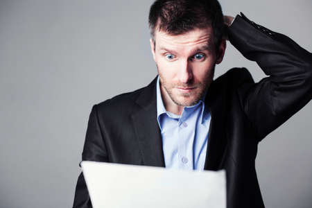 unhappy man: businessman reading document