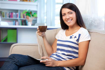 woman couch: Happy woman on couch with caffee and digital tablet
