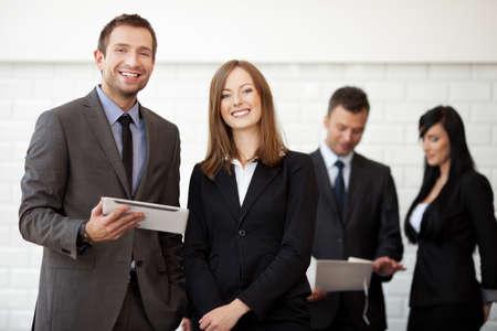 Incontro d'affari. Donna di affari ed uomo d'affari che stanno con sorridere digitale del ridurre in pani. Messa a fuoco selettiva con le persone in background.