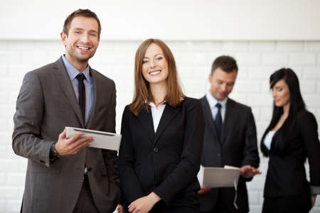 Business meeting. Businesswoman and businessman standing with digital tablet smiling. Selective focus with people in background. Foto de archivo
