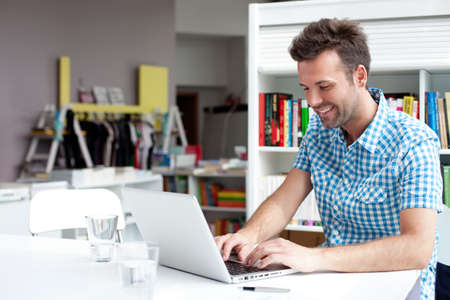 lidé: Šťastný student pracovat na notebooku v knihovně