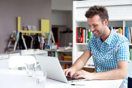 gente trabajando: Feliz estudiante de trabajo en la computadora portátil en la biblioteca Foto de archivo