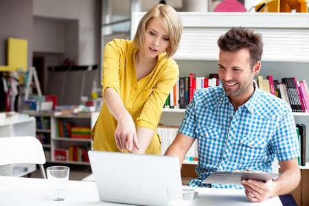 personas hablando: Dos gerentes de librerías que trabajan en la computadora portátil. Foto de archivo