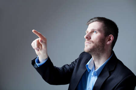 thirties: Portrait of handsome businessman pointing