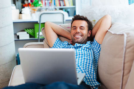 couch: Happy man relaxing with laptop on couch