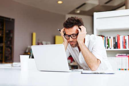 Zmęczony student lub biznesmen pracy z laptopem w biurze