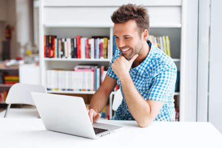 Casual man werken op de laptop in de bibliotheek