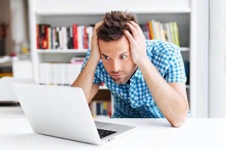man looking: Worried man looking on laptop