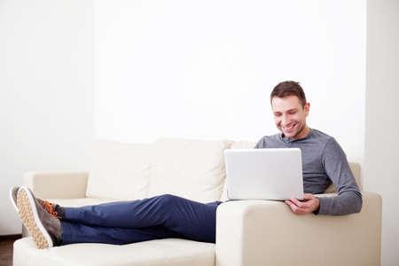 デジタル タブレットが付いているソファーに座っているハンサムな男
