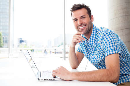 business casual: Happy man working on laptop