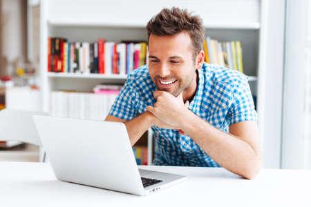 라이브러리에서 랩톱에서 작업하는 행복 한 학생