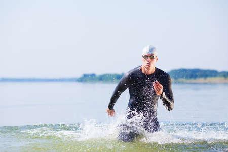 Triathlet aus dem Wasser auf Triathlon-Rennen läuft. Lizenzfreie Bilder