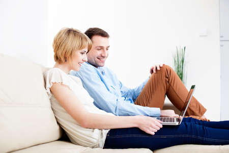 couple couch: Happy young couple sitting on couch using laptop
