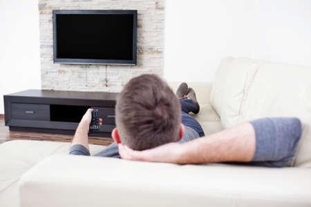 Einzelner Mann auf der Couch vor dem Fernseher, beim Kanalwechsel Standard-Bild - 53952552