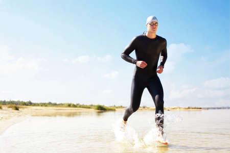 Triathlete running in to the water on triathlon race.