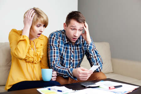 pay bill: Shocked couple paying bills at home