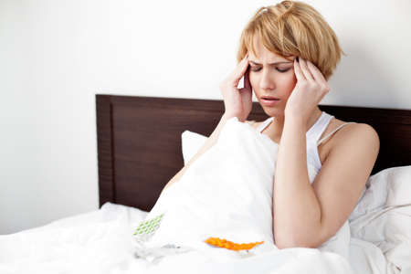 Sick woman lying in bed with headache