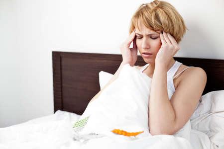 chory: Chora kobieta leży w łóżku z bólem głowy
