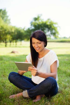 mujeres sentadas: Mujer feliz usando tableta digital en el parque, sentado en la hierba