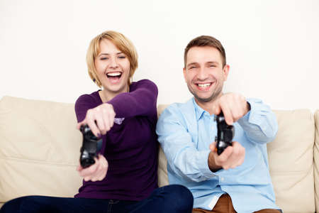 playing video games: Happy young couple playing video games at home.