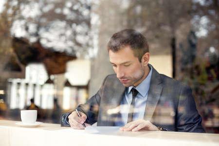 ビジネスマンのコーヒー ショップに座っている契約書に署名