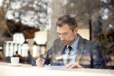 shop window: Businessman sitting in coffee shop, signing contract Stock Photo