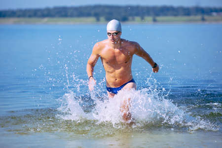 Traithlete running out of the water on triathlon race.