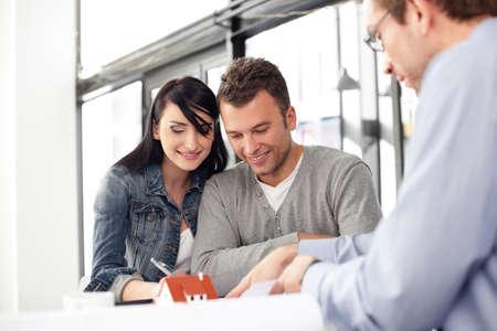 firmando: Joven pareja compra nueva casa. Reunión con el arquitecto.