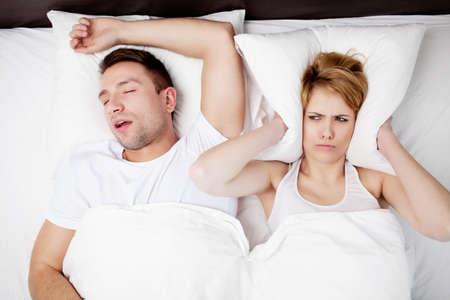 いびきをかく男性と若い女性。ベッドで寝ているカップル。