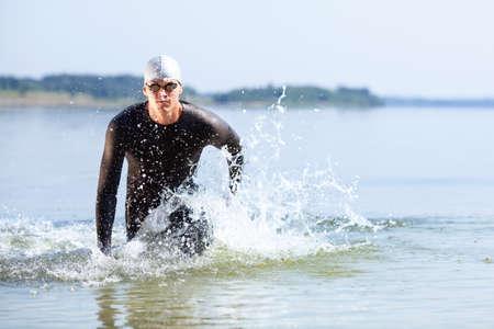 Triathlet aus dem Wasser auf Triathlon-Rennen läuft.