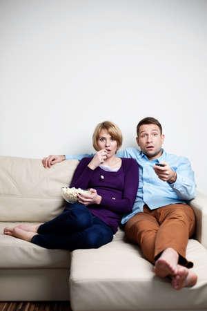 pareja viendo television: joven pareja de miedo viendo la televisión Foto de archivo