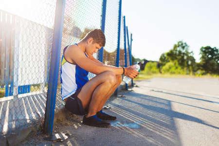 sediento: La motivación para correr. joven agotado descansando después de correr