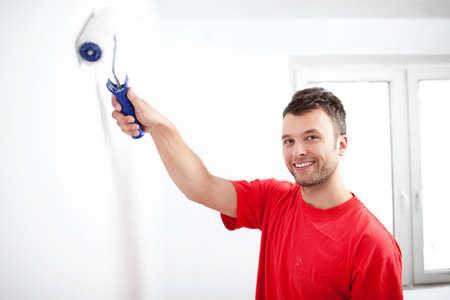 hombre pintando: pared de pintura joven feliz